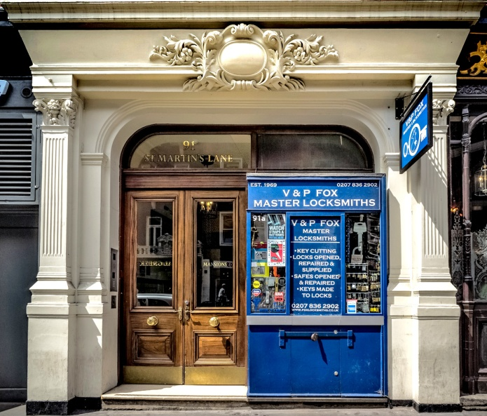 91a Charing Cross Road, City of Westminster, London WC2, 2015 • Tiny trad locksmith (est 1969) in big grand entrance.